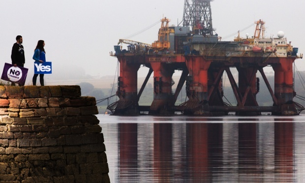 A yes campaigner and no campaigner during the Scottish independence referendum, at Cromarty Firth in the Scottish Highlands, with a drilling platform towering over them. Photograph: Murdo MacLeod/The Guardian Politics Blog